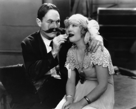 William Haines gives beauty tips to Marian Davies. Image: lkasdfj laksdjf