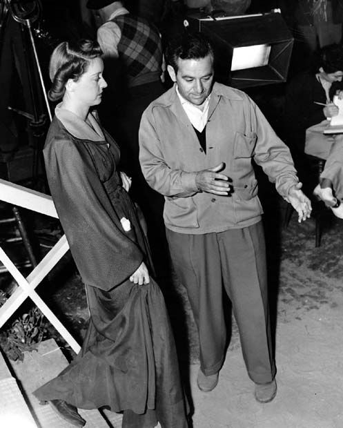Director William Wyler shows Bette Davis how to go down stairs while shooting someone. Image: Pinterest